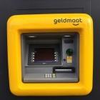 Geld pinnen in de buurt bij de uniforme gele geldautomaat
